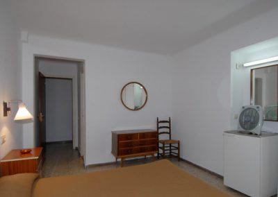 Jednoduchá dvojposteľová izba s chladničkou a malou kuchyňkou.